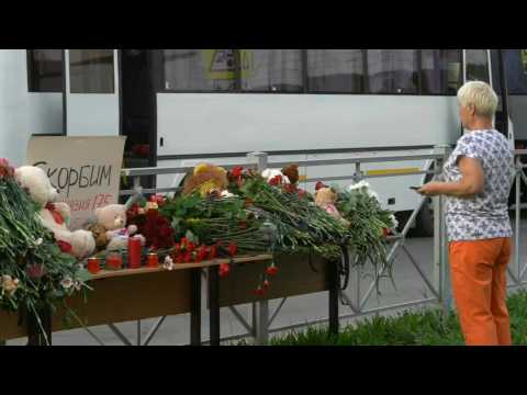 Russia: people lay flowers, soldiers stand guard outside Kazan school