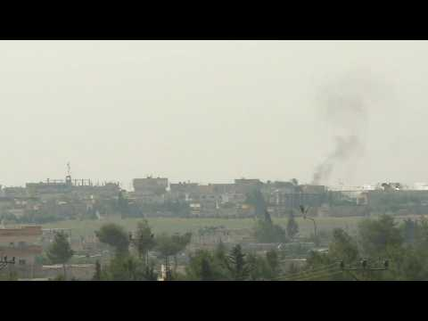 Smoke billows over the Syrian town of Tell Abyad, located just across the border with Turkey
