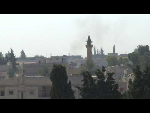 Smoke billows over Syrian border town of Tell Abyad as strikes sound