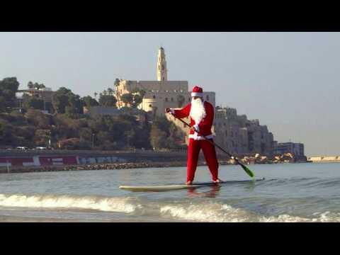 Santa Claus floats to Tel Aviv on his standup paddleboard