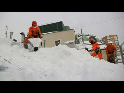 Moscow workers clean up snowy roofs and streets after record snowfall