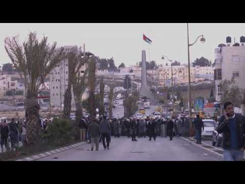 Palestinian security forces stop protesters before checkpoint