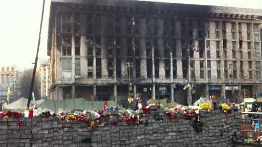 Illustration pour la vidéo Les restes d'un stock de pavés devant l'immeuble QG de la révolution, incendié au cours des combats