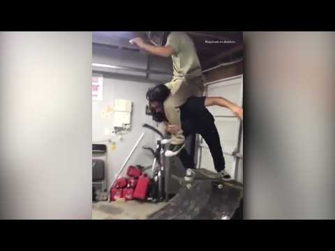 2 guys in a skateboard trying to drop into a half pipe!