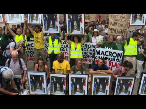Anti-G7 protesters showcase stolen Macron portraits