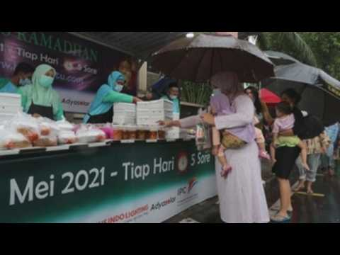 Indonesian Muslims queue for free iftar during Ramadan in Jakarta