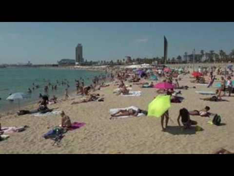 Crowds of people gather at Barcelona beaches