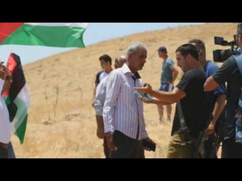 Palestinians protest against the appropriation of their land by Israeli settlers