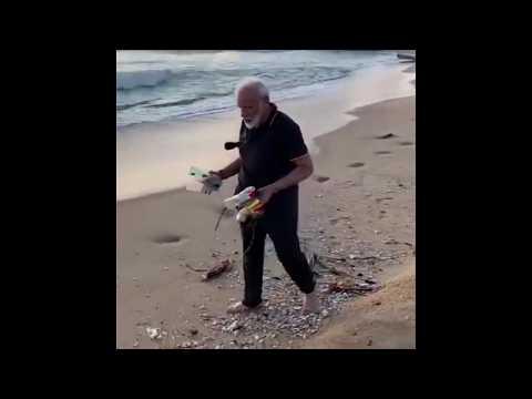 India Prime Minister Narendra Modi helps clear beach of rubbish