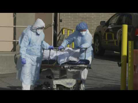 New York medics transport bodies to refrigerated truck, serving as temporary morgue
