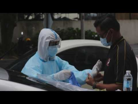 Malaysian health workers test people in quarantine for coronavirus