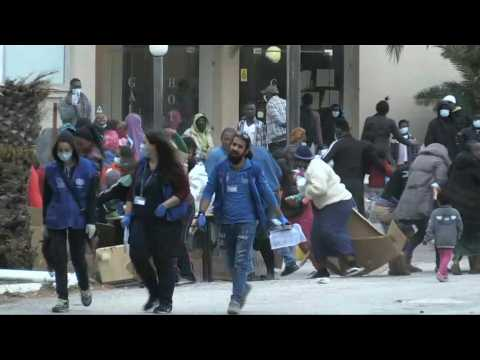 Migrants rush for aid supplies at quarantined Greek hotel