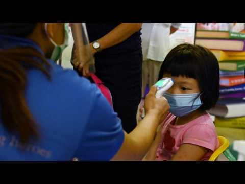 Pupils wearing face masks return to school in Singapore