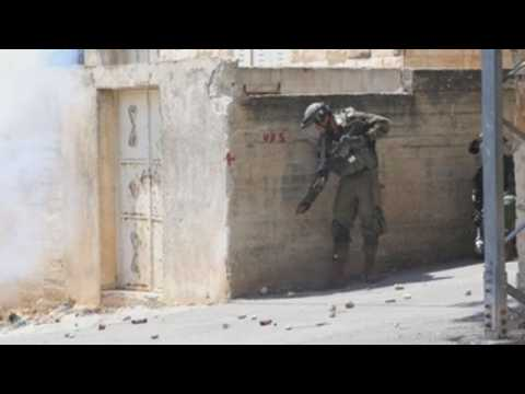 Palestinian demonstrators and Israeli soldiers clash in the West Bank