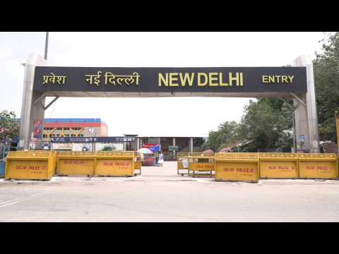 People wait at Delhi station as railways resume some operations