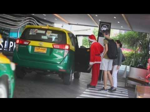 Bangkok mall staff welcome Christmas dressed as Santa Claus